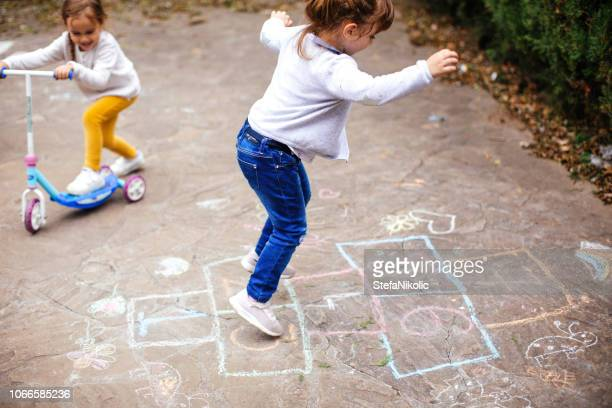 little girls play hopscotch on playground - hopscotch stock pictures, royalty-free photos & images
