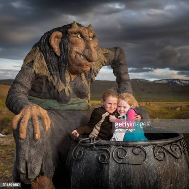 Little girls playing in a large caldron with statue of Gryla. Iceland