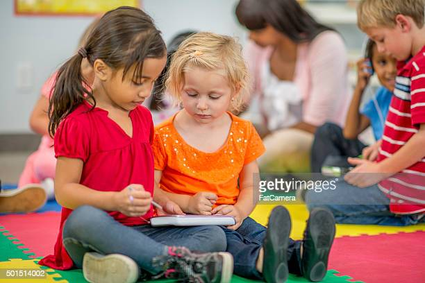 little girls playing on a tablet together - primary age child stock pictures, royalty-free photos & images