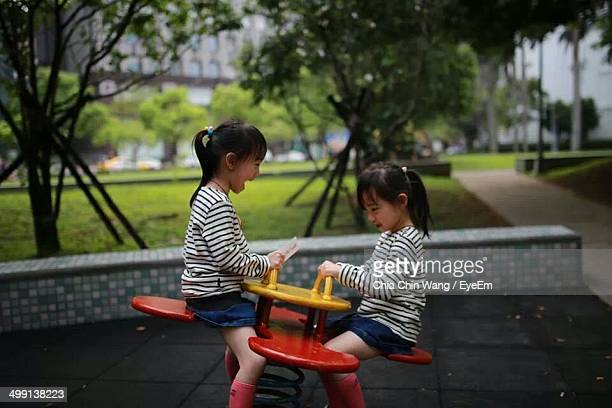 Little girls playing on seesaw in playground