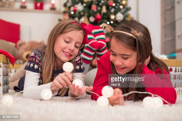 Little girls playing with Christmas lights