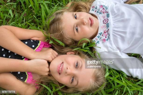 Little girls posing lying on the grass