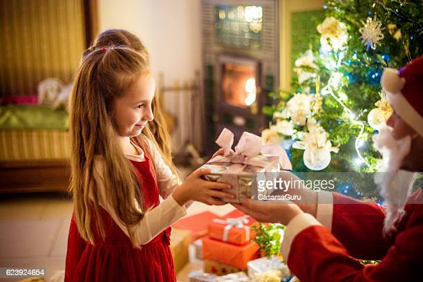Little Girls receiving Christmas Gifts from Santa