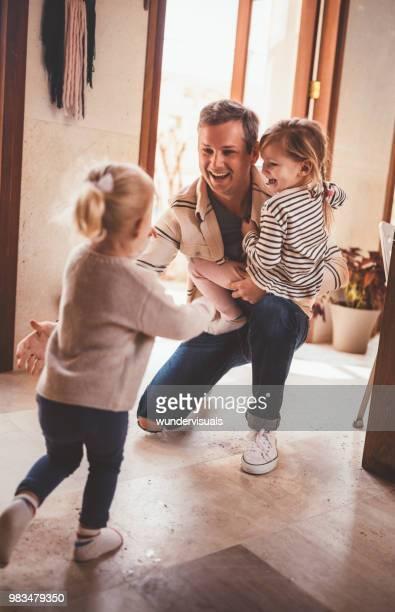 petites filles en courant vers le père quand rentrant du travail - essayer de marquer photos et images de collection