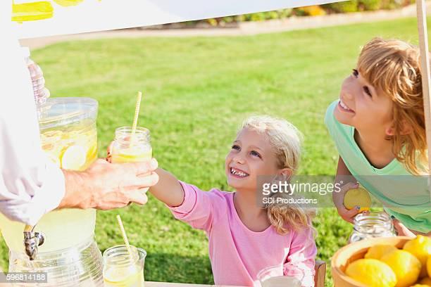 Little girls sell lemonade in front yard of home