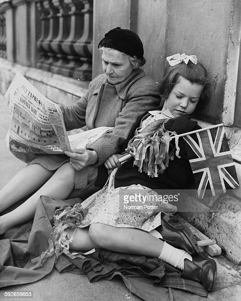 A little girls sleeps holding a Union Jack flag as her guardian reads the newspaper waiting for Queen Elizabeth II and the Duke of Edinburgh to pass...