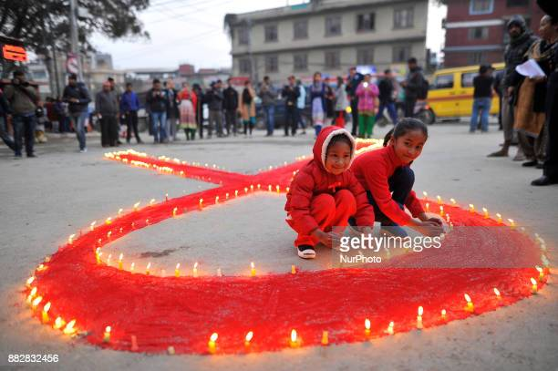 A little girls smiles as lit candles around the symbol of RED AIDS during Eve of World AIDS Day celebrated in Kathmandu Nepal on 1st Dec 2017 World...
