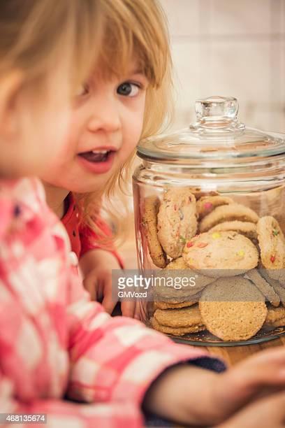 Little Girls Taking Oatmeal Cookies from a Jar
