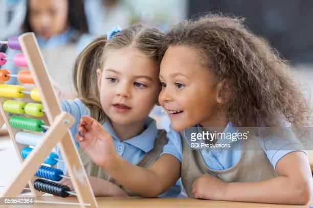 little girls use abacus during preschool - abaco imagens e fotografias de stock
