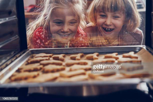 little girls waiting for christmas cookies to bake in the oven - preparation stock pictures, royalty-free photos & images