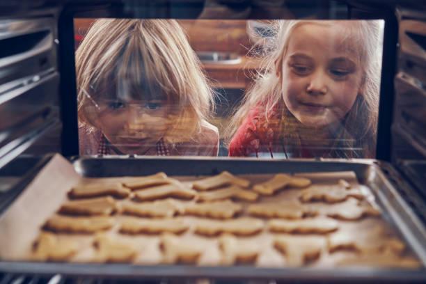 等待聖誕餅乾在烤箱裡烤的小女孩 - 焗 預備食物 個照片及圖片檔
