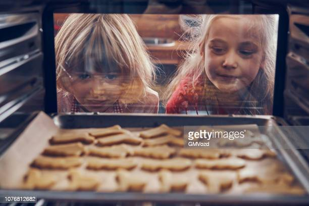 little girls waiting for christmas cookies to bake in the oven - baked stock pictures, royalty-free photos & images