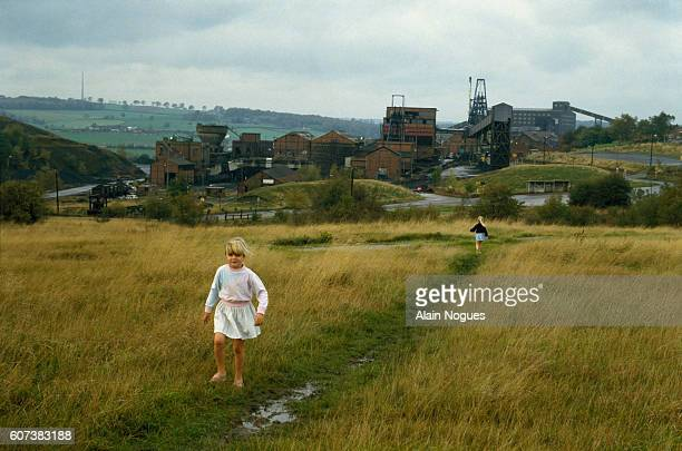 Little girls walk on a country path near an open-air mine in Yorkshire. At this time, a coal miners' strike was in its eighth month.