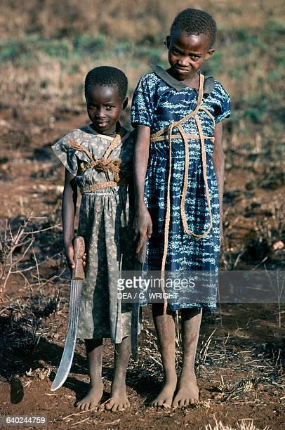 Little girls with a long knife Murera village near Mount Meru Kenya