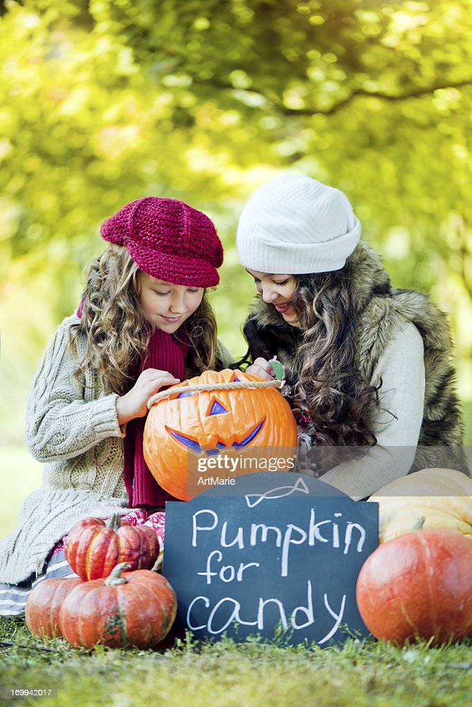 Little girls with pumpkins : Stock Photo