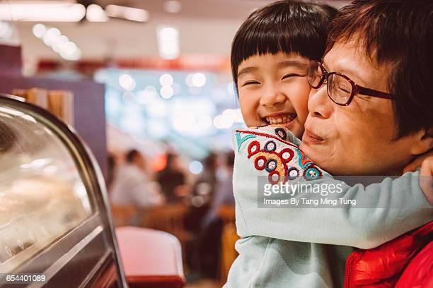 Little granddaughter hugging grandma joyfully