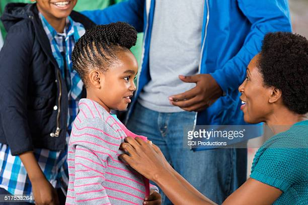 Little gril receives sweater at clothing drive