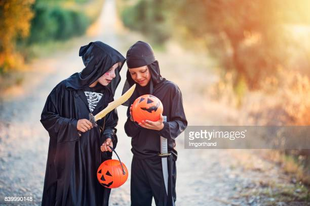 Little halloween boys comparing amount of candy