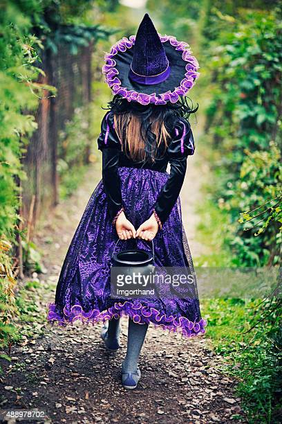 Little halloween witch walking with candy bucket