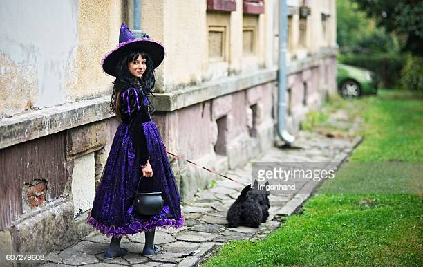 little halloween witch walking with her familiar - imgorthand stock photos and pictures