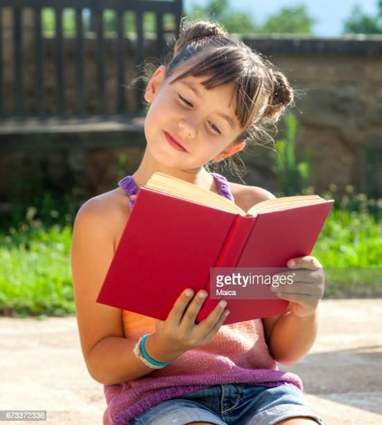 Niña feliz leyendo un libro