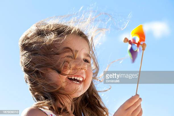 little happy girl with pinwheel - wind stockfoto's en -beelden