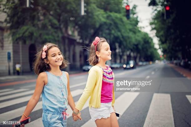 meninas felizes estão atravessando a rua na faixa de pedestre - cruzando - fotografias e filmes do acervo