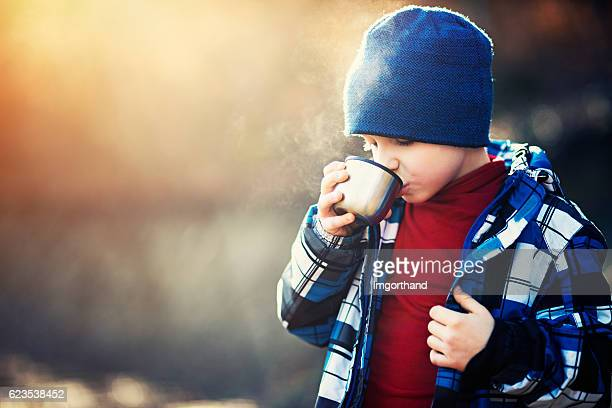 Little hiker drinking hot tea on sunny autumn day