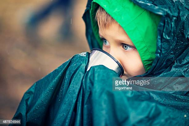 Little para excursionistas bebiendo té en la lluvia