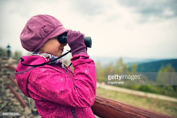 Little hiker girl looking at view with binoculars