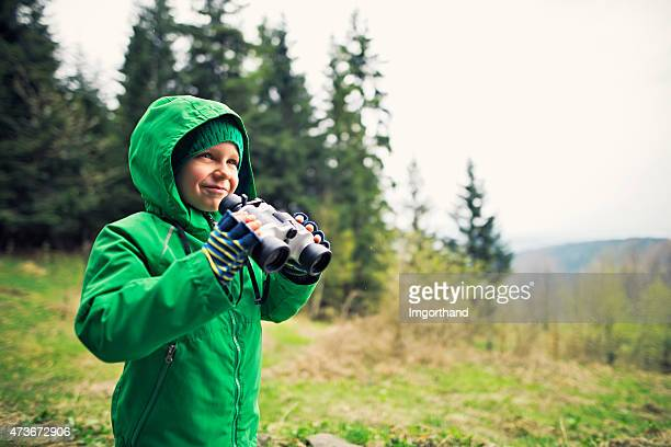 little hiker looking with binoculars - green coat stock pictures, royalty-free photos & images