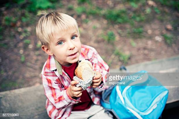 Little hiker resting and eating a sandwich