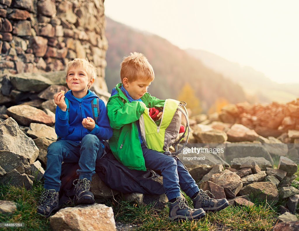 Little hikers resting and eating a snack : Stock Photo