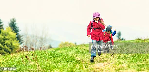 Little hikers running through a mountain meadow.