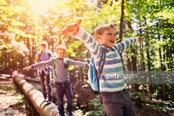 little hikers walking on a tree trunk  in forest - criança imagens e fotografias de stock