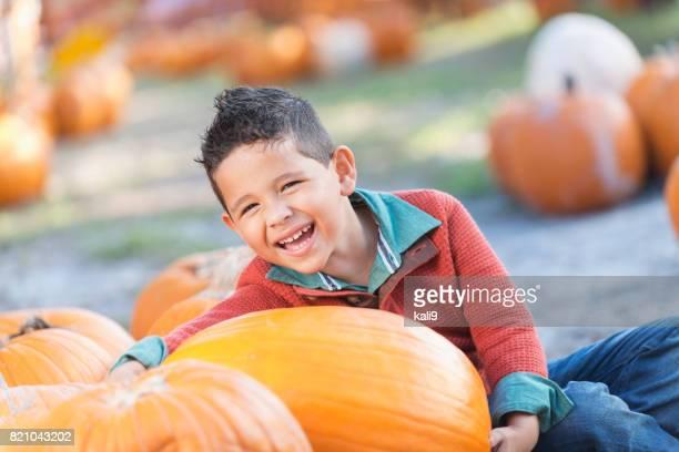 Little Hispanic boy in pumpkin patch