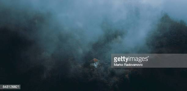 Little house on the slope during the withdrawal of a fog.