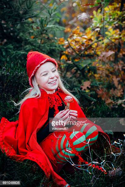 little imp sitting in forest, holding fly agaric - poisonous mushroom stock photos and pictures