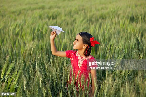 Little Indian girl holding a paper aero plane standing in wheat field