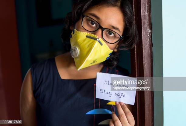 little indian girl holds a piece of paper in her hand with text stay home to give a message during corona virus pandemic. - india stock pictures, royalty-free photos & images