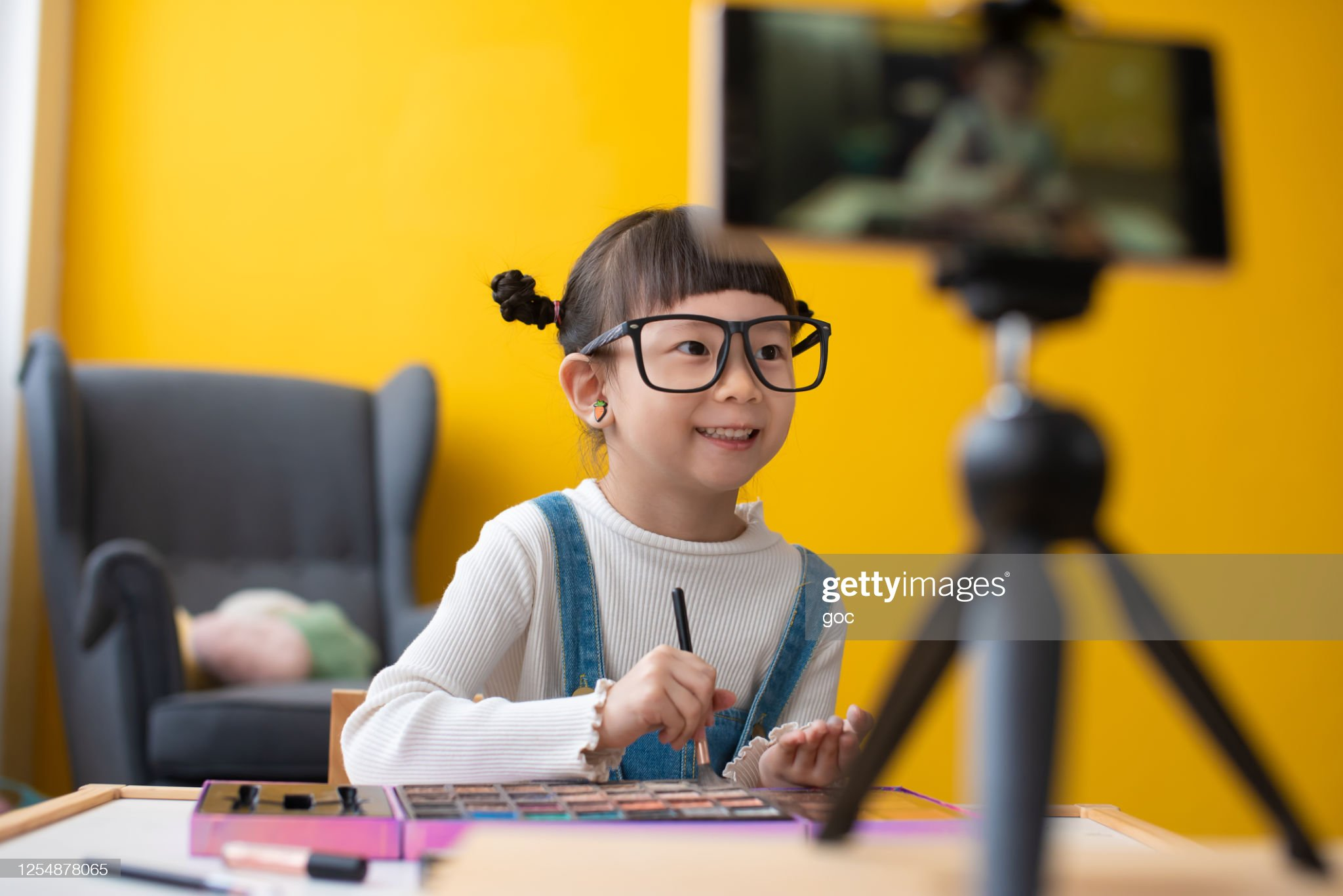 Little influencer teaching how to apply make-up for kids on live streaming video : Stock Photo