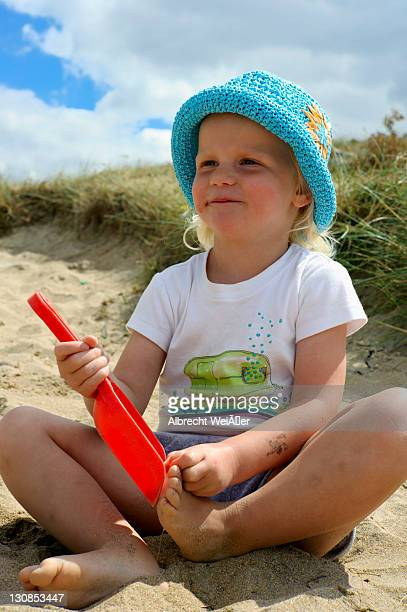 A little is sitting with a toy shovel on the beach, Bretagne, France, Europe