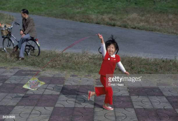 A little Japanese girl tries to fly a kite