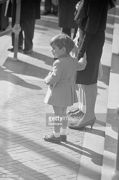 Little John F Kennedy Jr holds his mother's hand as he watches the pomp and ceremony as the casket containing the body of his dead father was carried...