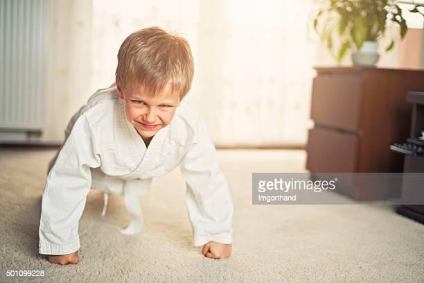 Little karate boy doing seiken pushups at home