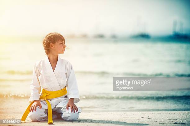 little karate girl sitting in seiza on beach - martial arts stock pictures, royalty-free photos & images