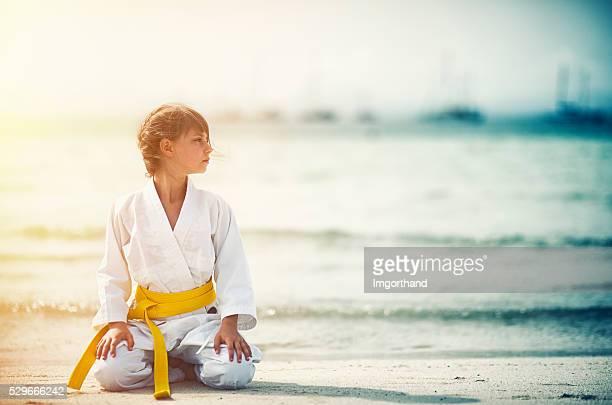 Little karate girl sitting in seiza on beach