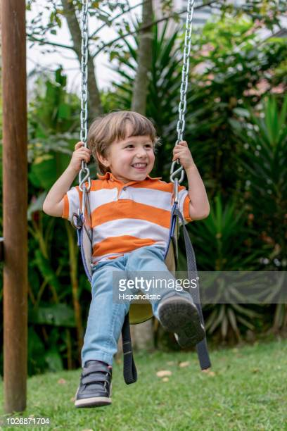 Little kid at the park on a swing smiling