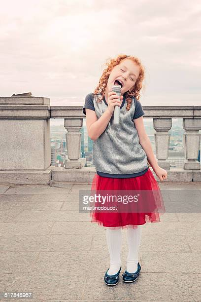 """little kid, big dreams. singing in front of cityscape. - """"martine doucet"""" or martinedoucet stock pictures, royalty-free photos & images"""