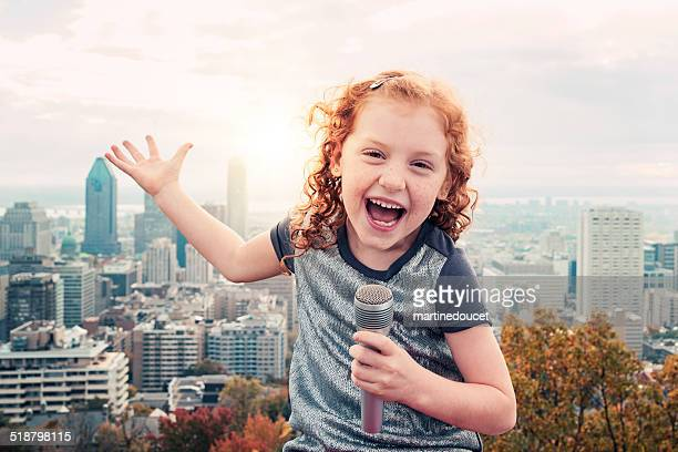 Little kid, big dreams. Singing in front of cityscape.